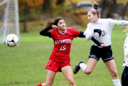 #13 Haley Wolfanger of Woodland clears a ball away from #15 Sydney Dzenutis of Northwestern during CIAC Class M girls soccer tournament action in Winsted Monday. Steven Valenti Republican-American
