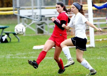 #6 Sydney Sanden of Northwestern kicks a ball past #17 Jillian O'Neil of Woodland during CIAC Class M girls soccer tournament action in Winsted Monday. Steven Valenti Republican-American