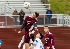 Naugatuck's Jay Barth #20 goes up high to head the ball against Newtown's Owen Baillargeon #10, with Naugatuck's Thomas Martins #7 looking on during the first round of the CIAC Class LL boys' soccer tournament between #22 Newtown and #11 Naugatuck at Naugatuck High School in Naugatuck on Tuesday. Naugatuck beat Newtown 1-0 and advances to the next round on Thursday. Bill Shettle Republican-American