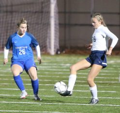 Morgan High School's Maura Kelly passes the ball to a teammate ahead of Lewis Mills High School's Makayla Issakhani during the CIAC Class M semifinal girls varsity soccer tournament game on Falcon Field in Meriden on Monday. Emily J. Reynolds. Republican-American