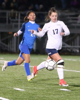 Morgan High School's Alyssa Smith battles Lewis Mills High School's Jazzy Sztyler-Magee for the ball during the CIAC Class M semifinal girls varsity soccer tournament game on Falcon Field in Meriden on Monday. Emily J. Reynolds. Republican-American
