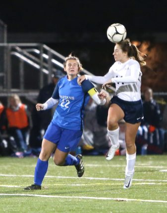 Morgan High School's Kylee Clifton heads the ball over Lewis Mills High School's Grace Kryzanski during the CIAC Class M semifinal girls varsity soccer tournament game on Falcon Field in Meriden on Monday. Emily J. Reynolds. Republican-American