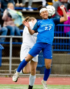 Lewis Mills' Jazzy Sztyler-Magee (27) gets pushed from behind by Plainfield's Alyssa Penkauskas (16) while going up to head the ball during their Class M soccer championship game Sunday at West Haven High School. Jim Shannon Republican American