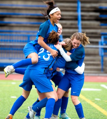 Lewis Mills' Grace Buchanan (5) is mobbed by teammates as they celebrate her overtime goal during their Class M soccer championship game with Plainfield Sunday at West Haven High School. Buchanan's goal would be the game winner in their 2-1 overtime win. Jim Shannon Republican American