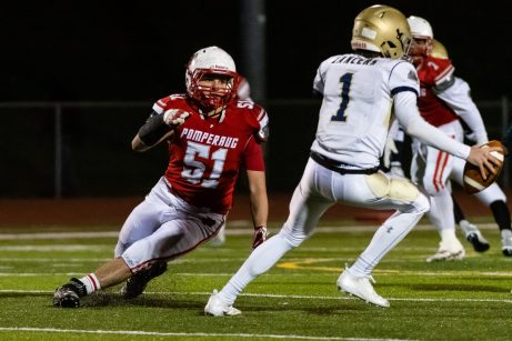 Pomperaug's Joseph Christiano #51 rushes in and forces Notre Dame of Fairfield quarterback John Fasset #1 out of the pocket during the regular season finale between Notre Dame of Fairfield and Pomperaug at Pomperaug High School in Southbury on Wednesday. Bill Shettle Republican-American