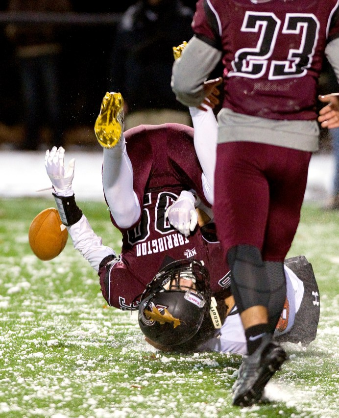 Torrington's Logan Kovall (39) coughs up the football after getting upended following his interceptions during their game against Watertown Wednesday at Torrington High School. Jim Shannon Republican American