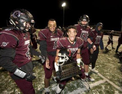 """Torrington senior John Rocha (7) celebrates with teammates after they were awarded """"The Helmet"""" for their 37-20 win over Watertown Wednesday at Torrington High School. Jim Shannon Republican American"""