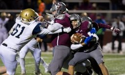 Naugatuck's John Mezzo (12) gets stopped at the line of scrimmage behind teammate Derek McGrath (56) and Platt's (51) during their Class L quarterfinal game Tuesday at Naugatuck High School. Jim Shannon Republican American
