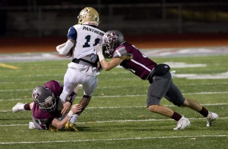 Naugatuck's Ernest Nyuggwila (22) and Jeff Schebell (24) tackle Platt's Tremayne Carter (11) after he intercepted a pass during their Class L quarterfinal game Tuesday at Naugatuck High School. Jim Shannon Republican American