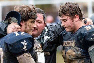 Larry Cafaro, center father of Ansonia players Tyler Cafaro #17, left, and Garrett Cafaro #86 hugs his sons telling them he loves them and is proud of them after Ansonia got beat by Bloomfield 26-19 during the Class S Semi-final game between Bloomfield and Ansonia at Ansonia High School in Ansonia on Sunday. Bill Shettle Republican-American