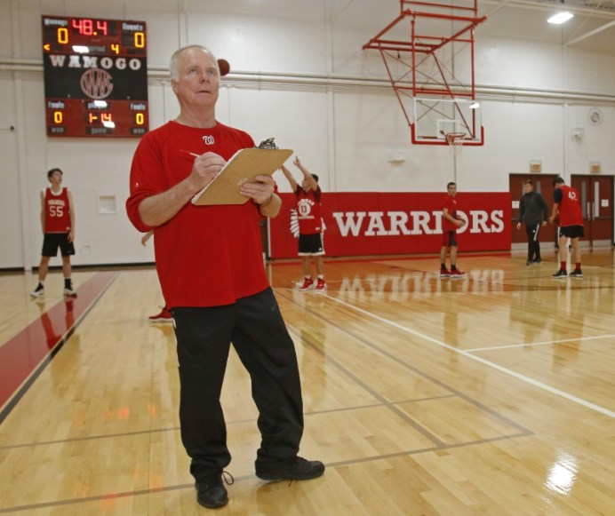 Wamogo's basketball coach Greg Hunt checks off on pre-season drills in the newly renovated gym Monday. Michael Kabelka Republican-American