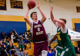 Sacred Heart center Connor Tierney #0 goes up for a baseline shot against Holy Cross' Kyle Moser #30 during the annual Waterbury Boys Basketball Jamboree at Kennedy High School in Waterbury on Sunday. Bill Shettle Republican-American