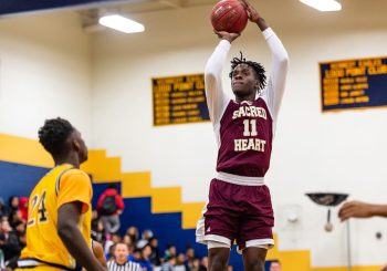 Sacred Heart forward Jamaal Waters #11 shoots a jumper in front of Kennedy's Jay Turner #24 during the annual Waterbury Boys Basketball Jamboree at Kennedy High School in Waterbury on Sunday. Bill Shettle Republican-American