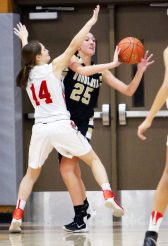 #25 Ava DeLucia of Woodland High tries to pass as #14 Morgan Matyoka of Wolcott High defends during 2nd quarter NVL basketball action in Wolcott Monday. Steven Valenti Republican-American