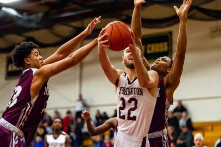 Torrington's Kevin Dixon #22, drives to the basket splitting in between the Naugatuck defense of Robert Sanders #23, left, and Avery Hinnant #4 behind during a NVL Boys Basketball game between Naugatuck and Torrington at Torrington High School in Torrington on Thursday. Torrington held on to win in a close one 47-46 over Naugatuck. Bill Shettle Republican-American