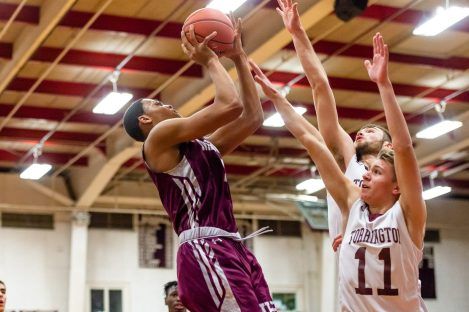 Naugatuck's Avery Hinnant #4 goes up for a baseline jumper against Torrington defenders TJ Callabrese #11, and Kevin Dixon #22, behind, during a NVL Boys Basketball game between Naugatuck and Torrington at Torrington High School in Torrington on Thursday. Torrington held on to win in a close one 47-46 over Naugatuck. Bill Shettle Republican-American