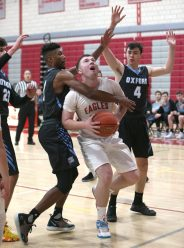 Wolcott High School's Jack Drewry tries to take a shot over Oxford High School's Charles Flowers, left, and Patrick Mucherino during the varsity basketball game in Wolcott on Wednesday night. Emily J. Reynolds. Republican-American