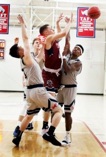#0 Tyler Arbuckle of Taft pass of the rebound as #3 Perry Zai and #4 CJ Brito-Trinidad of Kent defends during basketball action in Watertown Wednesday. Steven Valenti Republican-American