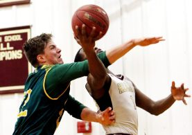 #22 Jack Greene of Holy Cross fouls #1 Nate Tabor of Sacred Heart under the hoop during basketball action in Waterbury Thursday. Steven Valenti Republican-American