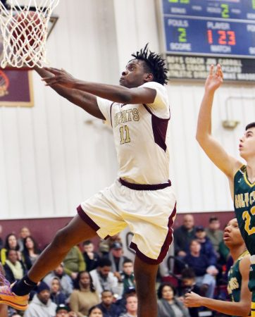 #11 Jamaal Waters of Sacred Heart goes to the hoop over #23 Kyle Lombardi of Holy Cross during basketball action in Waterbury Thursday. Steven Valenti Republican-American