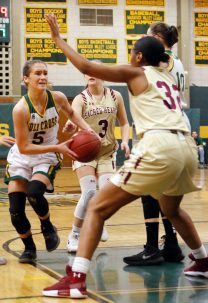 Holy Cross' Allie Brown (#5) drives the lane as Sacred Heart's Nevaeh Jones (#32) defends Friday night during NVL action at Holy Cross High School. Michael Kabelka / Republican-American