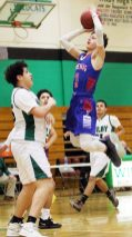#3 Jackson Baker of Nonnewaug High puts up a shot over #25 Anthony Abraham of Wilby High during basketball action in Waterbury Monday. Steven Valenti Republican-American
