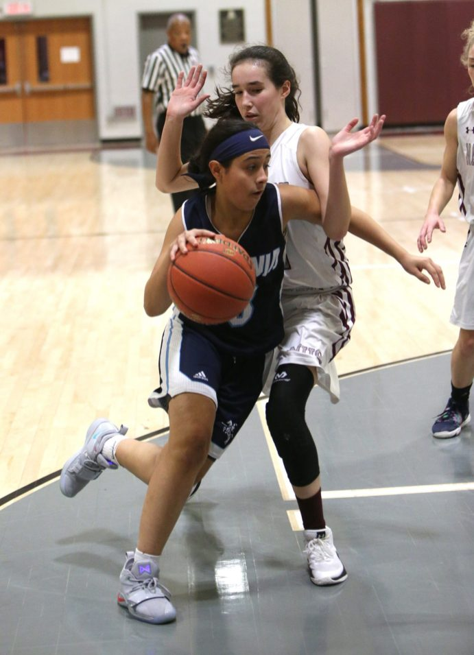 Ansonia High School's Hailey Bellido drives to the basket through Naugatuck High School's Kaylee Jackson during the girls varsity basketball game in Waterbury on Wednesday night. Emily J. Reynolds. Republican-American