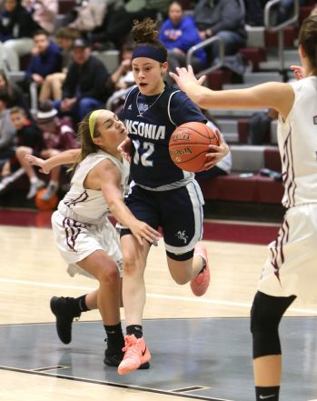 Ansonia High School's Larissa Rodriguez drives to the basket through Naugatuck High School's Mia Rotatori during the girls varsity basketball game in Waterbury on Wednesday night. Emily J. Reynolds. Republican-American