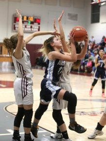 Ansonia High School's Natasha Rivera goes up for a shot over Naugatuck High School's Hailey Russell, left, and Sarah Macary during the girls varsity basketball game in Waterbury on Wednesday night. Emily J. Reynolds. Republican-American