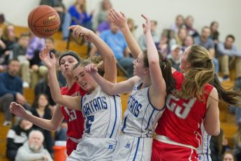 Northwestern's Emma Propfe (13), left, and Jana Sanden (23) battle for a rebound with Lewis Mills' Brianna Pelchar (5) and Emily Hunt (11) during their NVL match up Friday at Lewis Mills. Jim Shannon Republican American