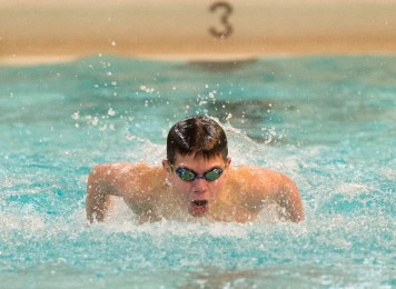 Woodland's Jake Arisian competes in the 100 butterfly during their meet with Holy Cross Friday at the John Reardon Pool at Kennedy High School in Waterbury. Jim Shannon Republican American