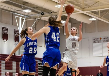 Naugatuck's Sarah Wisniewski #0 puts up a running one hander as she drives down the lane against Bristol Eastern's Sage Scarritt #25 and Avery Arbuckle #42, during a second round tournament game in the Girls Class L Basketball Championships between Bristol Eastern and Naugatuck at Naugatuck High School in Naugatuck on Thursday. Bill Shettle Republican-American