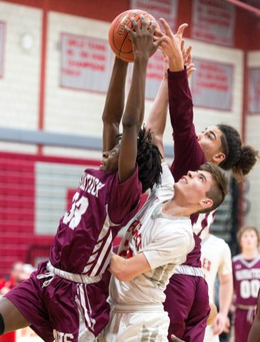 Naugatuck's Ese Onakpoma (33) and Andrew Robertson Brian Perzhilla (11) battle for a rebound with Wolcott's (21) during their NVL game Tuesday at Wolcott High School. Jim Shannon Republican American