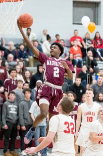 Naugatuck's Gwayne Fisher (2) lays in a shot in front of Wolcott's Jack Drewry (32) during their NVL game Tuesday at Wolcott High School. Jim Shannon Republican American