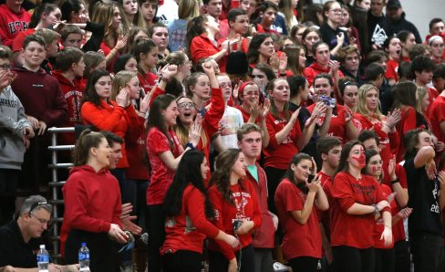 Northwestern High School boys varsity basketball fans cheer for the team on the floor during the game at Northwestern against Gilbert High School on Friday night. Emily J. Reynolds. Republican-American