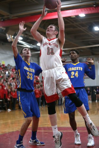 -Northwestern High School's Owen Maltby goes up for a shot over Gilbert High School's Dylan Crowley and Carlos Sarmiento during the boys varsity basketball game at Northwestern on Friday night. Emily J. Reynolds. Republican-American