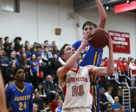 Gilbert High School's Dylan Crowley tries to block a shot by Northwestern High School's Brandon North during the boys varsity basketball game at Northwestern on Friday night. Emily J. Reynolds. Republican-American