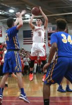 Northwestern High School's Levi Delaney goes up for a shot over Gilbert High School's Dylan Crowley and Juan Sarmiento during the boys varsity basketball game at Northwestern on Friday night. Emily J. Reynolds. Republican-American