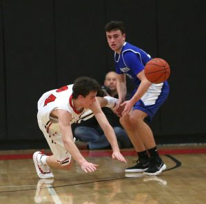 Cheshire High School's Eli Battipaglia dives for a loose ball ahead of Southington High School's Jake Napoli during the boys varsity basketball game at Cheshire High School on Friday, Feb. 15, 2019. Emily J. Reynolds. Republican-American