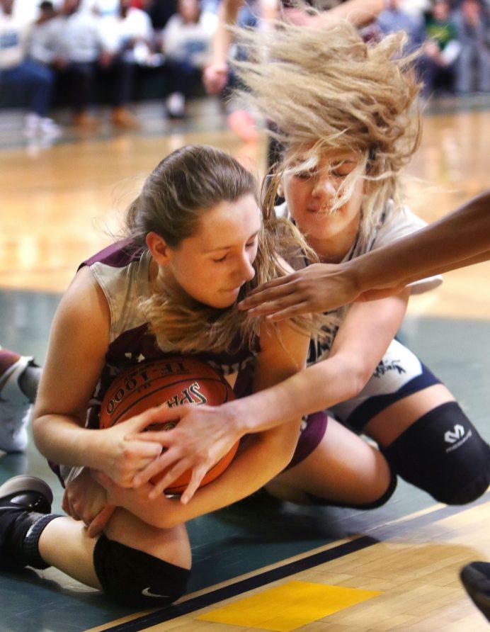 #3 Brielle Behuniak of Naugatuck and #21 Natasha Rivera of Ansonia battle for the loose ball during overtime at the NVL girls basketball tournament in Waterbury Saturday. Steven Valenti Republican-American