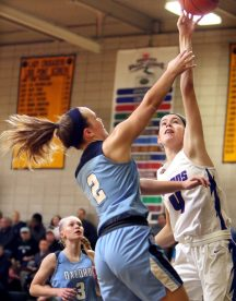#4 Olivia Heslin of St. Paul puts up a basket over #2 Kelly Shpak of Oxford during the NVL girls basketball tournament in Waterbury Saturday. Steven Valenti Republican-American