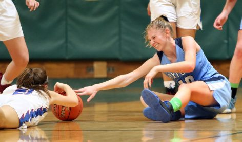 #10 Molly Sastram of Oxford battles for the loose ball with #21 Catherine Ciampi of St. Paul during the NVL girls basketball tournament in Waterbury Saturday. Steven Valenti Republican-American