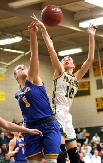 #10 Alyssa Hebb of Holy Cross High puts up a shot over #1 Kolby Sirowich of Seymour High during the NVL girls basketball tournament in Waterbury Saturday. Steven Valenti Republican-American