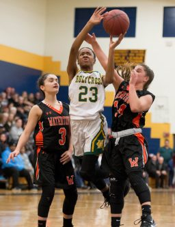 Holy Cross' Kayla Howard (23) lays up a shot between Watertown's Marissa Forino (3) and Chloe DeFeo (34) during their NVL semi-final game Monday at Kennedy High School in Waterbury. Jim Shannon Republican American