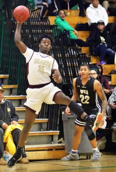 #11 Jamaal Waters of Sacred Heart saves the ball from going out of bounds as #22 Marquan Watson of Waterbury Career Academy defends during NVL semi final basketball action in Waterbury Monday. Steven Valenti Republican-American
