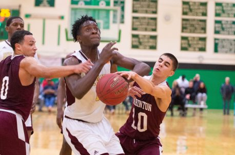 Sacred Heart's Jamaal Waters (11) gets fouled by Torrington's Joel Villanueva (10) while Villanueva goes for a block during their NVL tournament finals game held Wednesday at Wilby High School in Waterbury. Jim Shannon Republican American