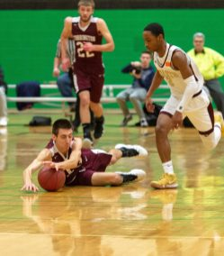 Torrington's CJ Root (13) dives for a loose ball in front of Sacred Heart's Lorenzo Washington during their NVL tournament finals game held Wednesday at Wilby High School in Waterbury. Jim Shannon Republican American