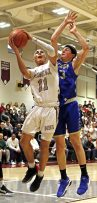 Naugatuck's Jack Kuligowski (11) puts up a shot as Newtown's Robert Disibio (33) defends during the opening round of division III boys basketball tournament at Naugatuck High School Thursday night. Naugy defeated Newtown to advance. Michael Kabelka / Republican-American
