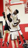 #11 Jamaal Waters with the help of #0 Connor Tierney of Sacred Heart High blocks #34 Evan Gutowski of Trumbull High during the CIAC quarterfinal in Southbury Monday. Steven Valenti Republican-American