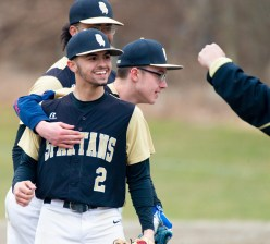 WCA's Jacob Torres (2) is congratulated by players and coaches after coming in to strike out the final batter in their 1-0 won over Wolcott Tuesday at Washington Park in Waterbury. Jim Shannon Republican American